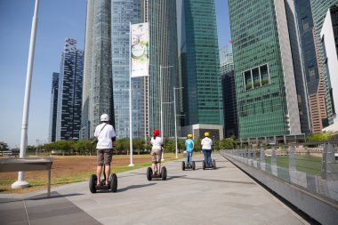 People on an electric scooter on the waterfront in Singapore