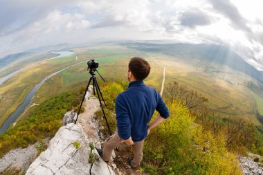 Photographer on top of the mountain takes on the camera