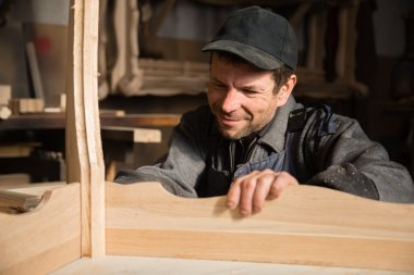 Smiling carpenter examines produces furniture