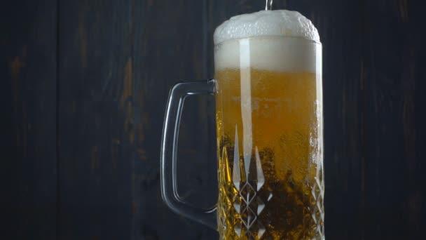Nalil pivo do skla přes tmavé dřevěné pozadí.