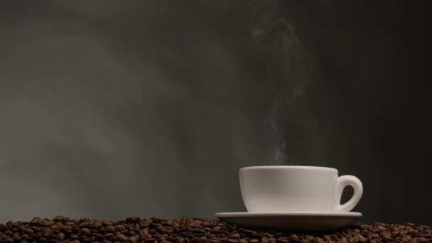 Tasse Kaffee mit Dampf. dunkler Hintergrund mit Kaffeebohnen