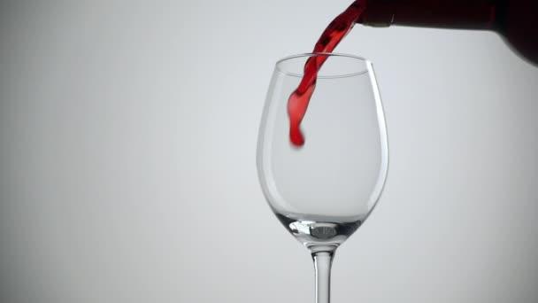 Zpomalený záběr nalévá červené víno do skla