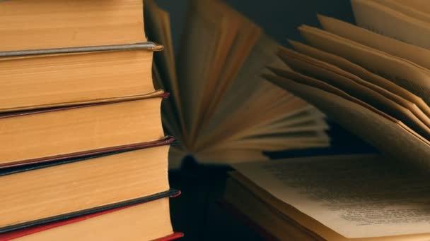 Staré knihy o dřevěné paluby stůl a tmavým pozadím