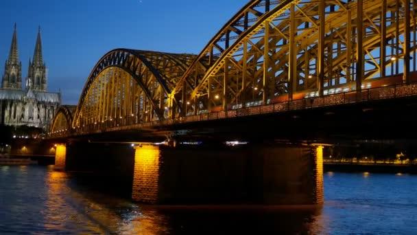 Gotische Kathedrale und eiserne Brücke über den Rhein nach Sonnenuntergang. Köln, Deutschland
