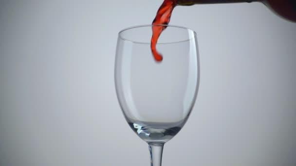 Öntés vörös bor az üveg fehér háttérhez képest. Lassú mozgás