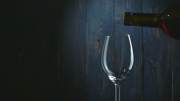 Szakadó vörös bor a pohárba, sötét fából készült háttér. Lassú mozgás