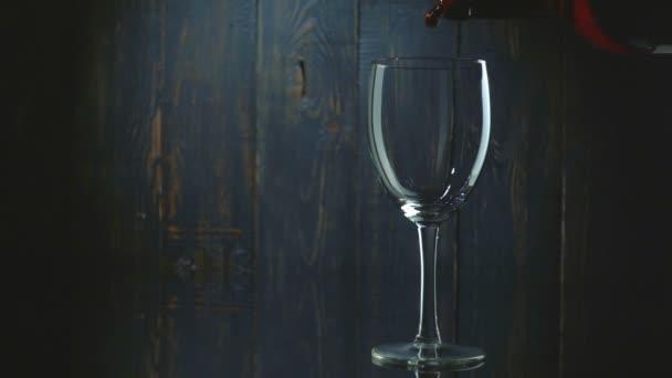 Červené víno přelijete do skleněné tmavé dřevěné pozadí. Zpomalený pohyb