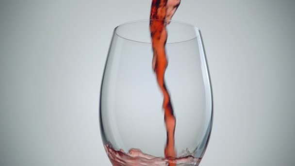 Pouring red wine into the glass over white background. Slow motion