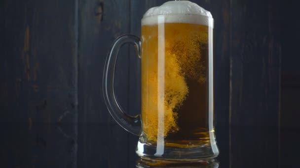 Bier in Glas über dunklem Holzgrund gießen. Zeitlupe