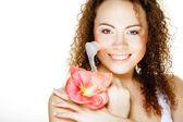Krásné lázeňské dívka drží růžový květ a štětec