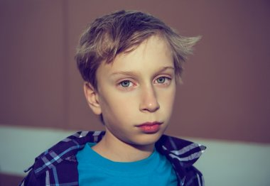 Portrait of a beautiful blond boy looking very sad and frustrated