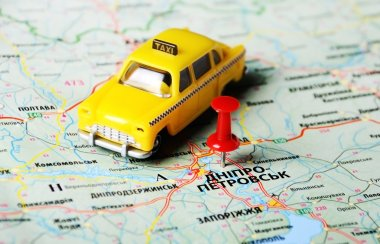 map with red pin and a taxi toy