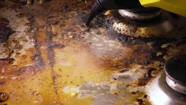 Handdampfreiniger reinigt eine Gaskochfläche