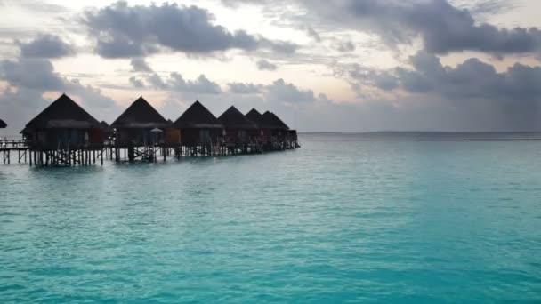 Domy nad mořem za úsvitu. Maledivy