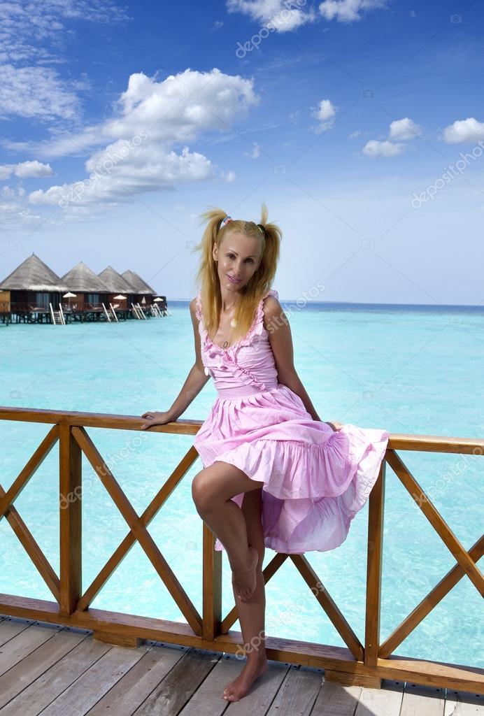 junges sch nes m dchen steht in rosa sommerkleid auf die sonnenterrasse der villa auf dem wasser. Black Bedroom Furniture Sets. Home Design Ideas