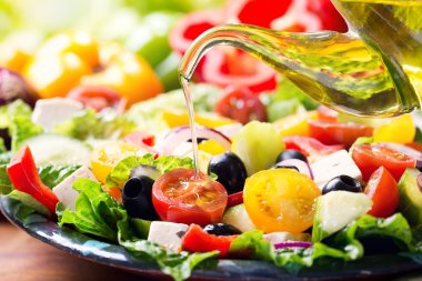 Olive oil pouring into plate of fresh greek salad stock vector
