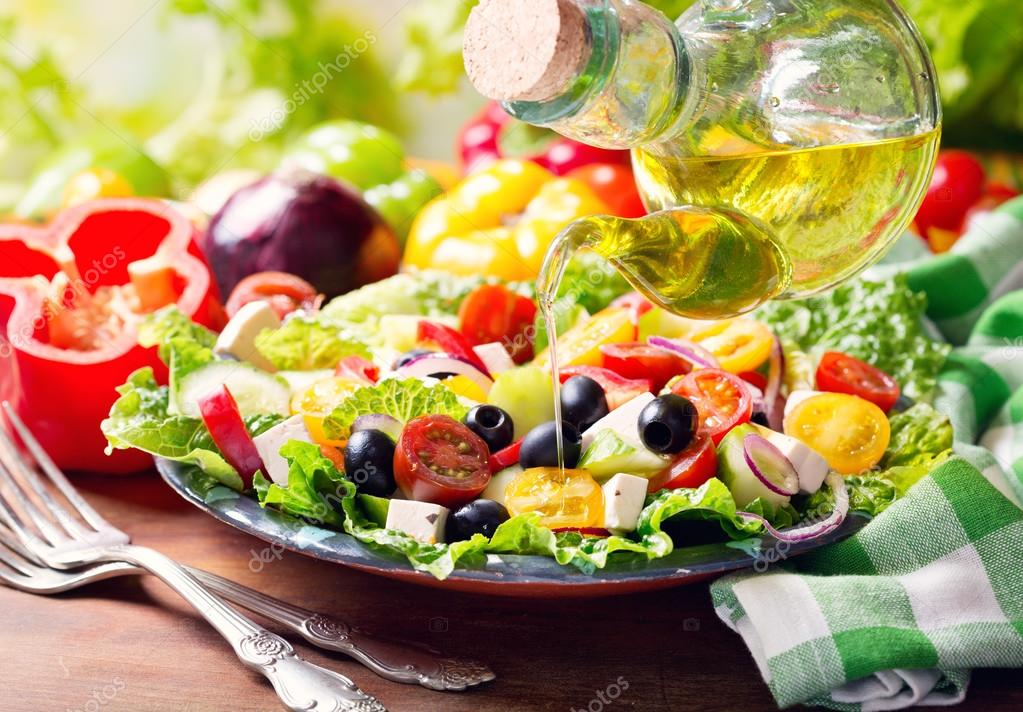 Olive oil pouring into plate of greek salad