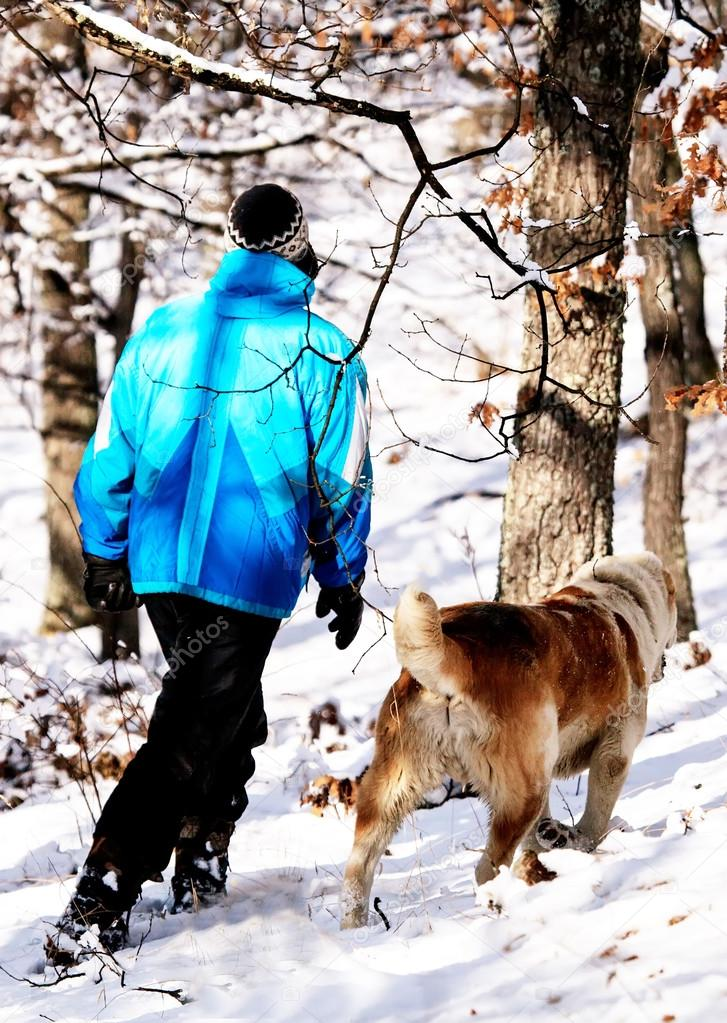 man and dog in winter forest