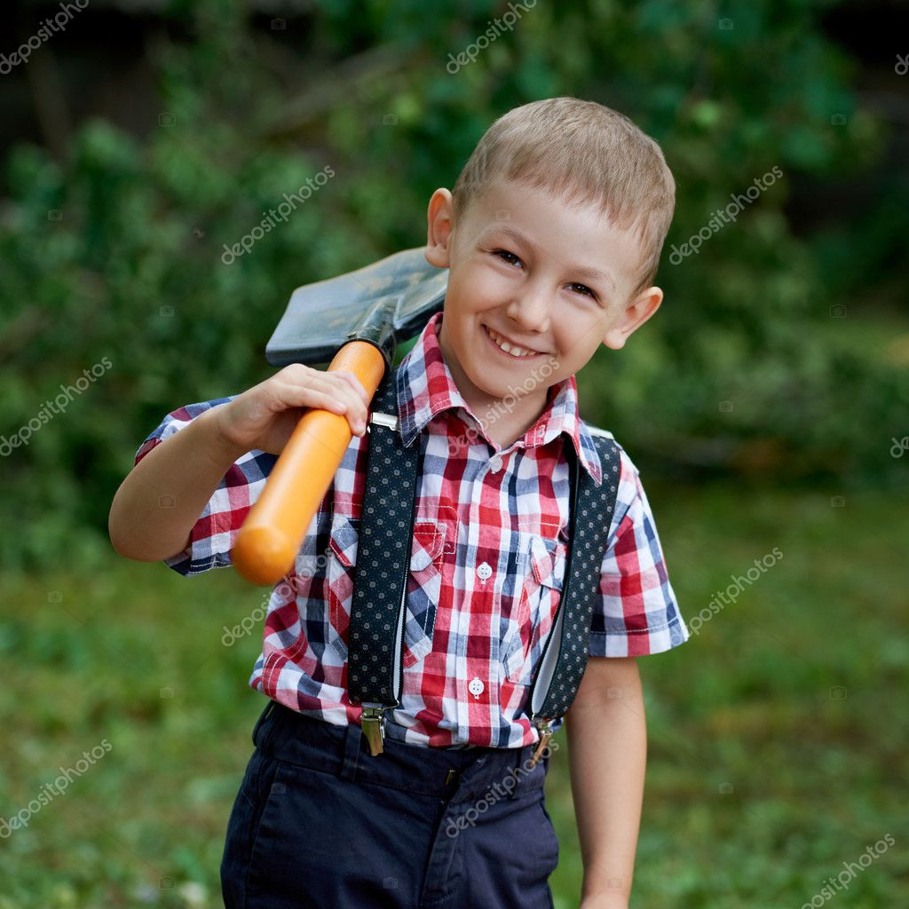 funny boy with shovel in garden