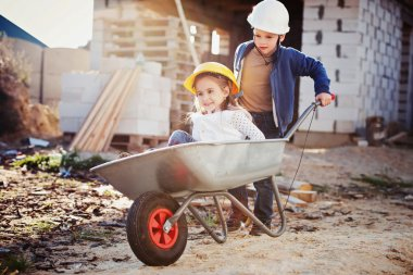 boy and girl playing on construction site