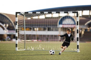 boy plays football on stadium
