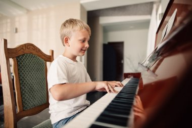 little happy boy plays piano