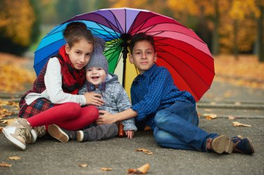 happy children under rainbow umbrella
