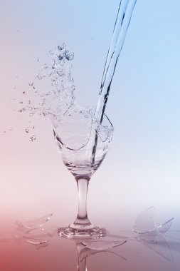 Clear water pour out of bottle splash into glass and spill with