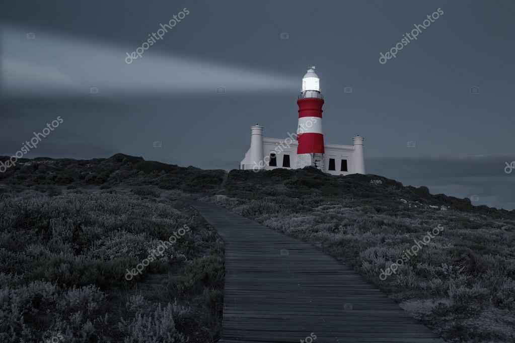 Lighthouse with shining light in darkness and dark blue clouds a