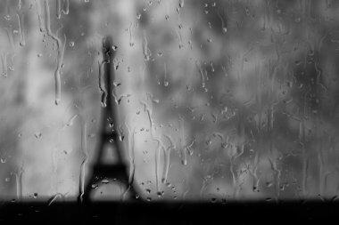 Eiffel tower seen through wet window in rain storm