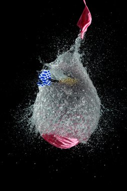 Balloon filled with water is popped with dart to make a mess