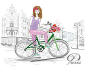 Fashion girl rides a bicycle the streets of the old town.