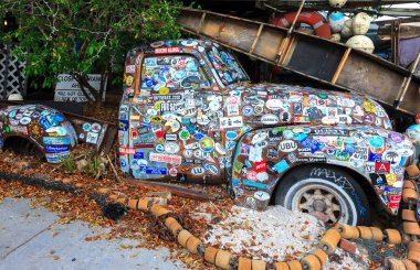 Old car covered with a variety of stickers