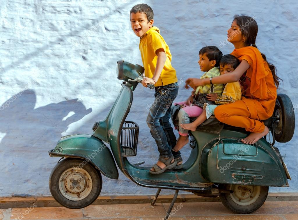 An unidentified Indian children play with an old scooter in Jais
