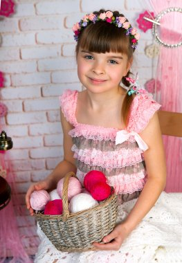 Cute little girl in pink fishnet dress and wreath holding a bask