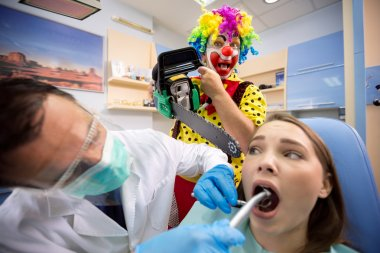 Girl on dental treatment with crazy clown behind