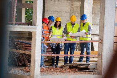 Team of experts studying blue print at construction site