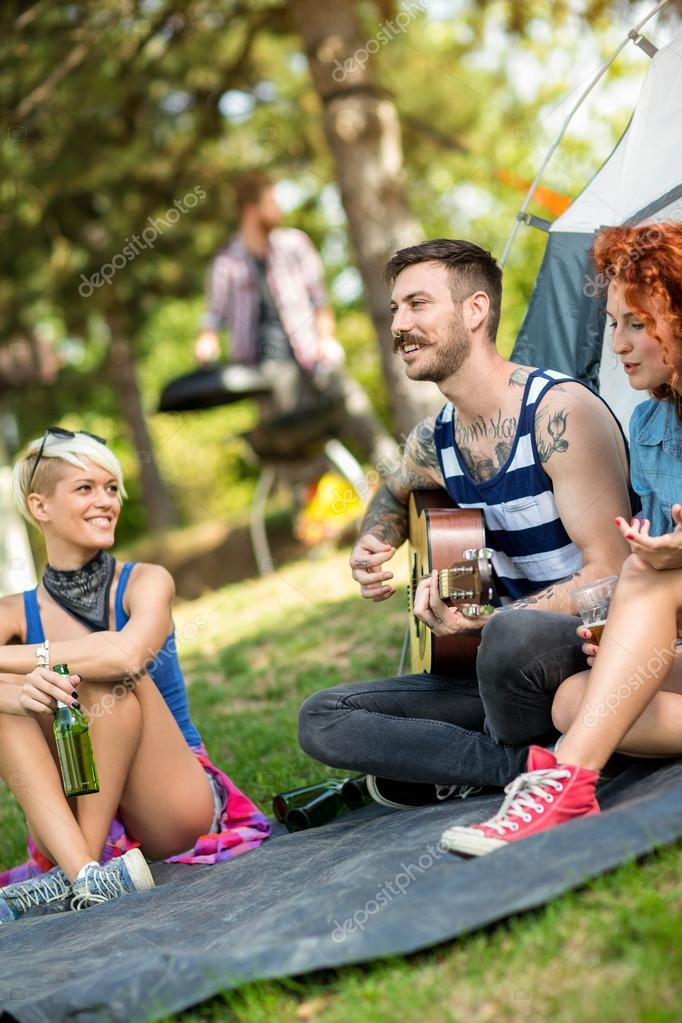 Guy play guitar and girls enjoys in front of tent at camp