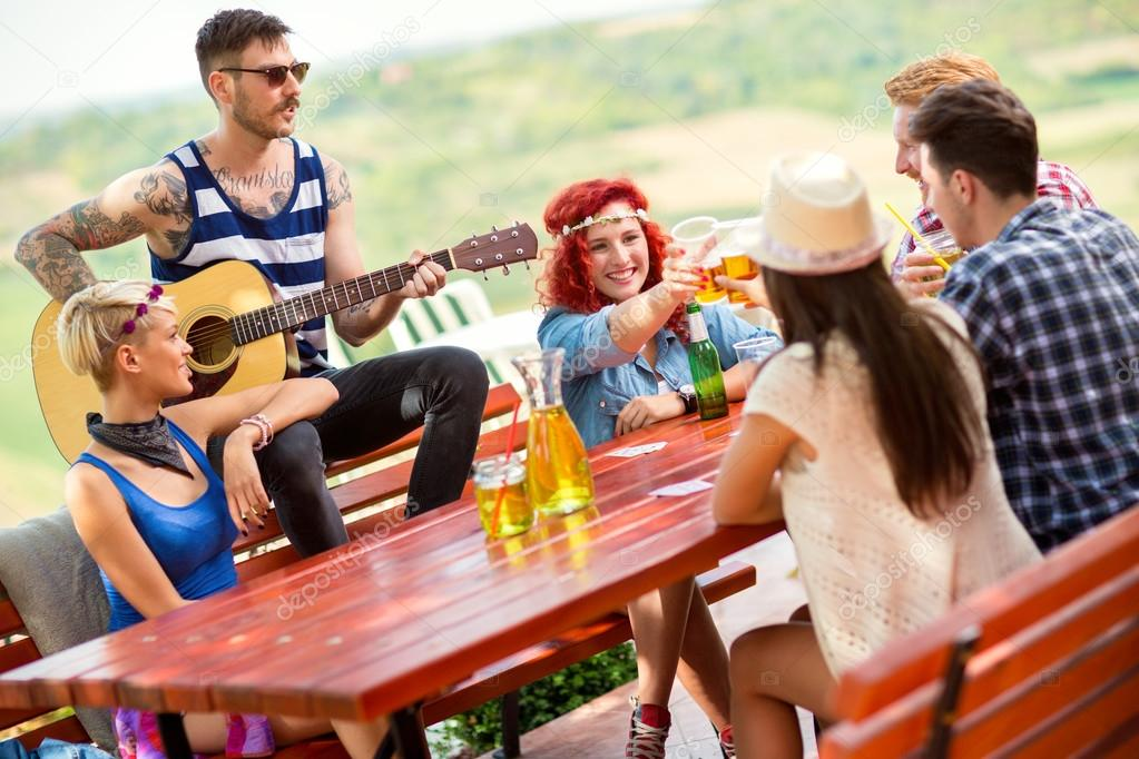 Girls toast with glasses of beer while tattooed boy play guitar