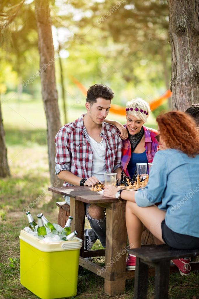 Boys and girls in pair play chess and drinks cold beer in nature