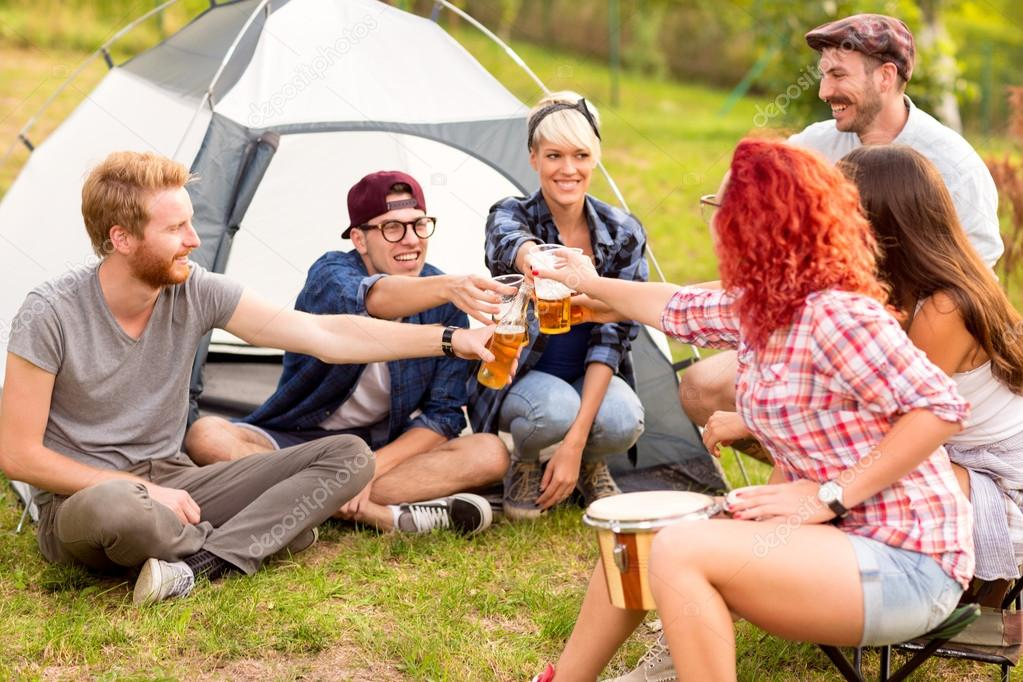 Male and female tapping with beer in front of tent
