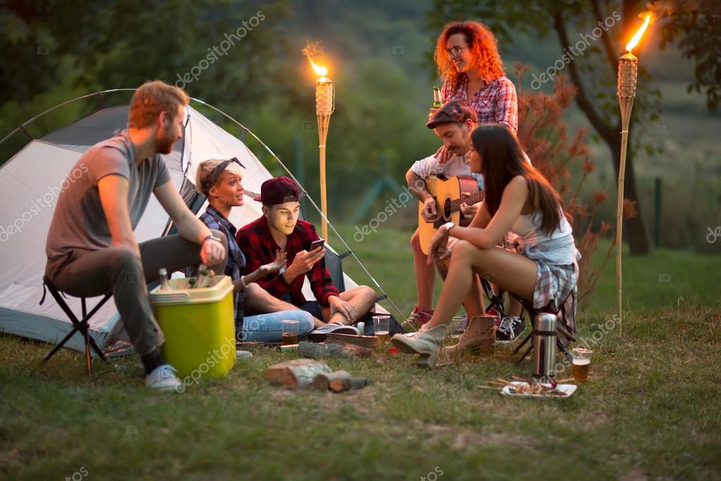Socializing youngsters in front of tent at night