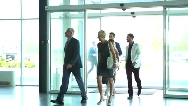 Diverse team of business people walk around their light and modern office building.