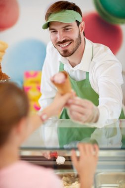 Salesman in confectionery provides ice cream to girl