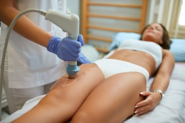 attractive woman in beauty salon on localized anti fat treatment
