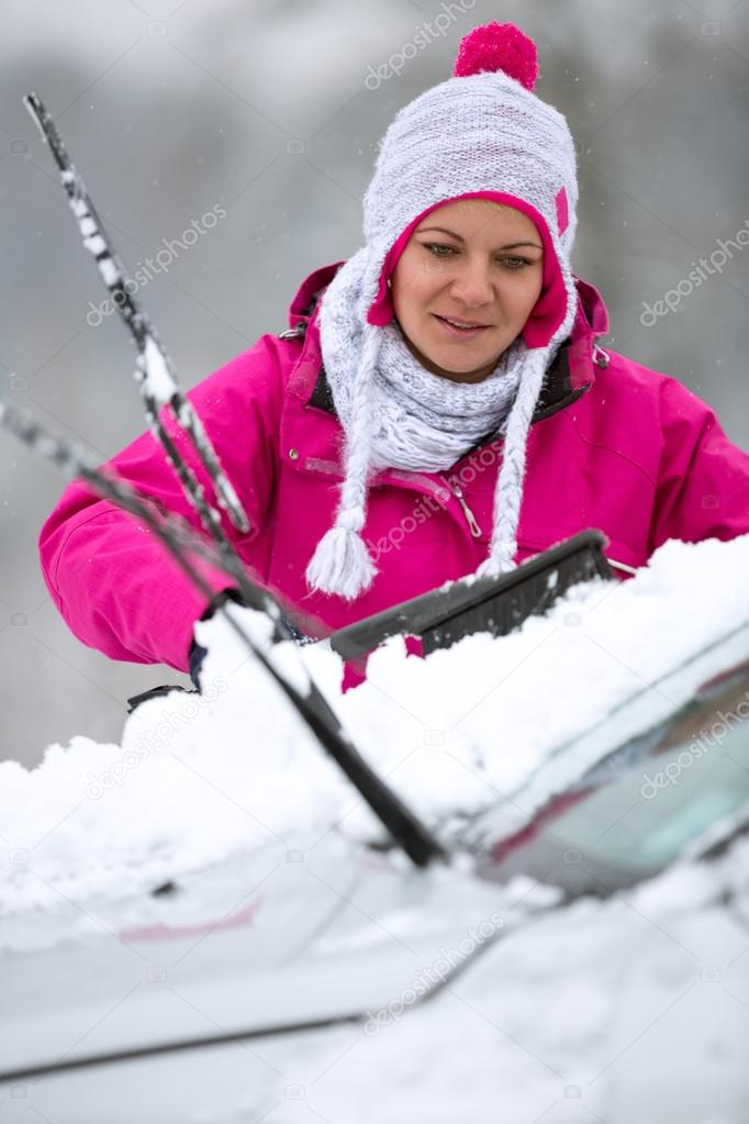 girl cleaning snow car from