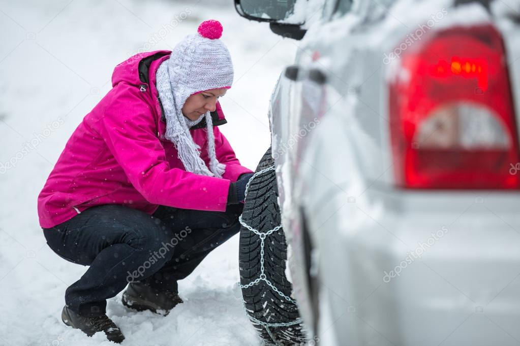woman putting snow chains