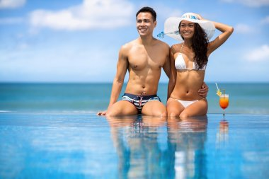 Asian young couple sitting in swimming pool under sunny summer