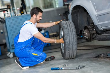 Auto mechanic removing wheel of a car