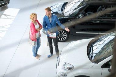 Friendly car dealer showing young women new car